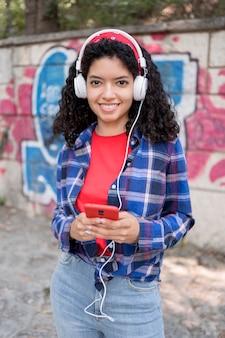Medium shot happy girl posing with headphones