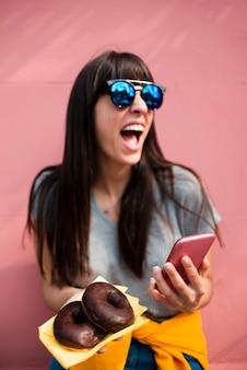 Ragazza felice del colpo medio con le ciambelle e lo smartphone