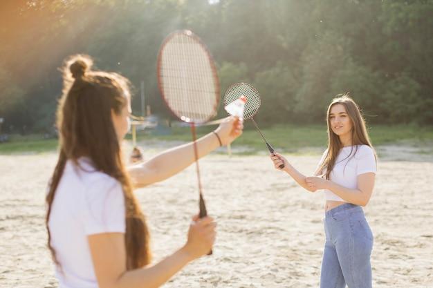 Средний снимок счастливых девушек, играющих в бадминтон