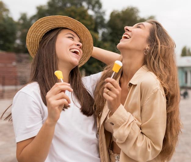 Средний снимок счастливых девушек с конфетами