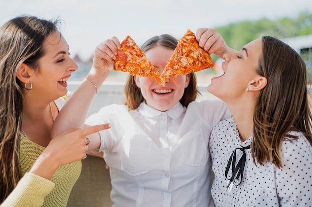 Medium shot happy girls with pizza slices