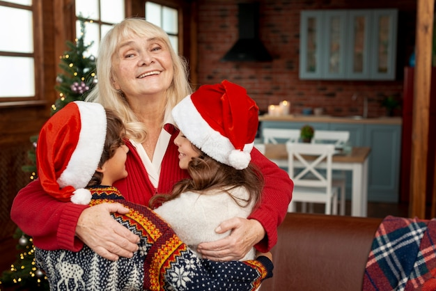Medium shot happy grandmother hugging grandchildren