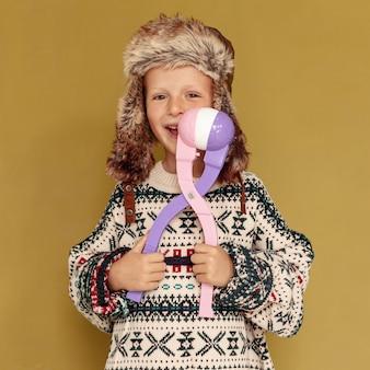 Средний снимок счастливый ребенок с игрушкой и шляпой