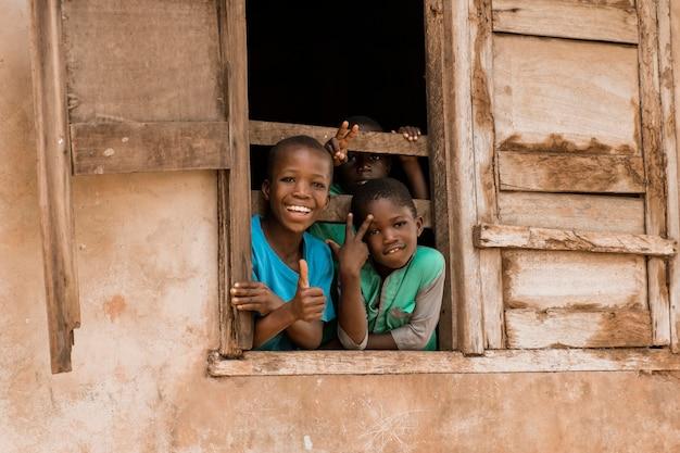 Bambini felici del colpo medio alla finestra