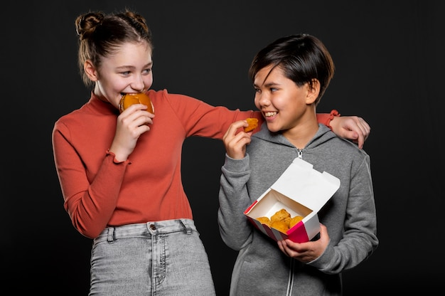 Medium shot happy kids with fast food
