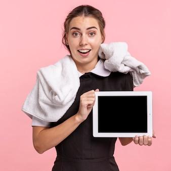 Средний снимок счастливая горничная держит планшет