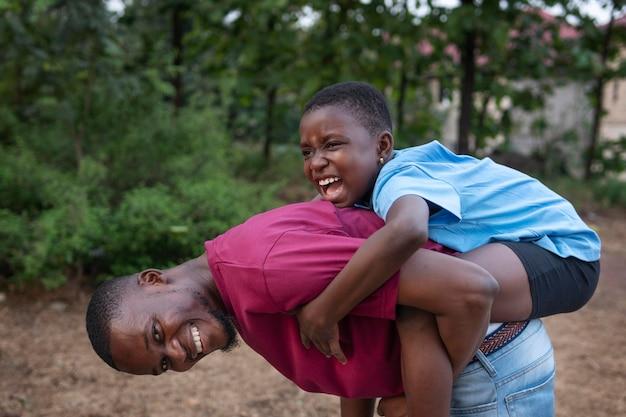 Medium shot happy man carrying kid