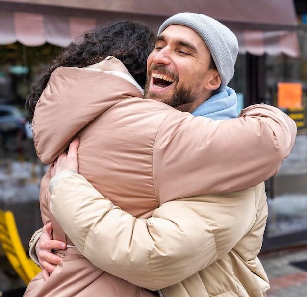 Uomo felice del colpo medio che abbraccia donna