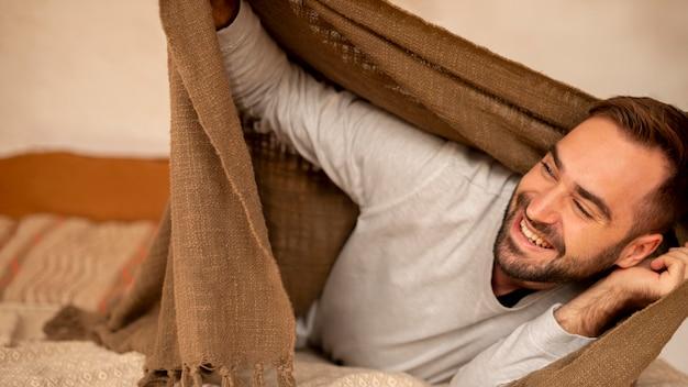 Средний снимок счастливый человек с одеялом