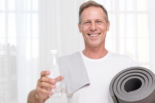 Средний снимок счастливый человек с ковриком для йоги и полотенцем