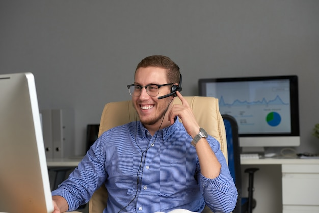 Medium shot of happy manager working in call centre