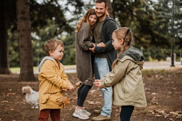 Medium shot happy parents watching children