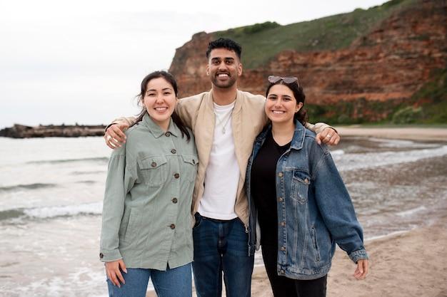 海辺でミディアムショットの幸せな人々