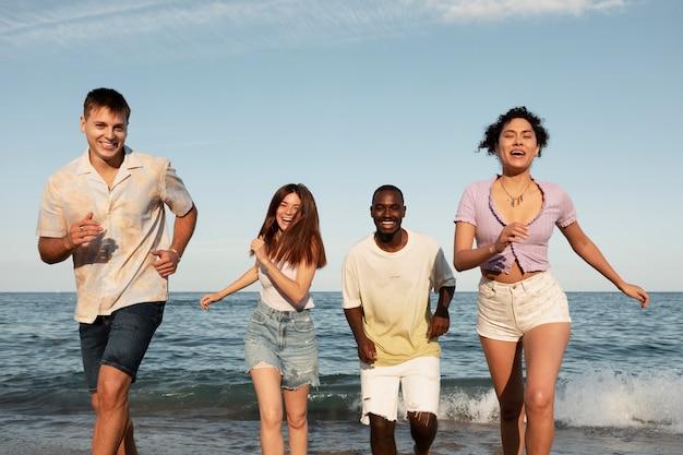 해변에서 중간 샷 행복한 사람들