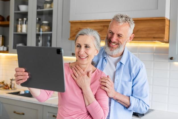 Medium shot happy senior couple with tablet