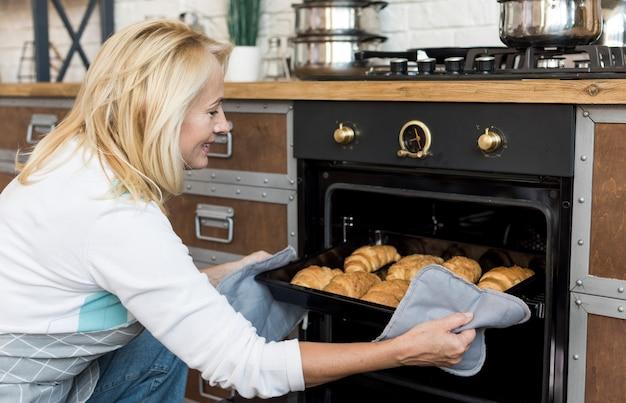 Medium shot happy woman baking croissants