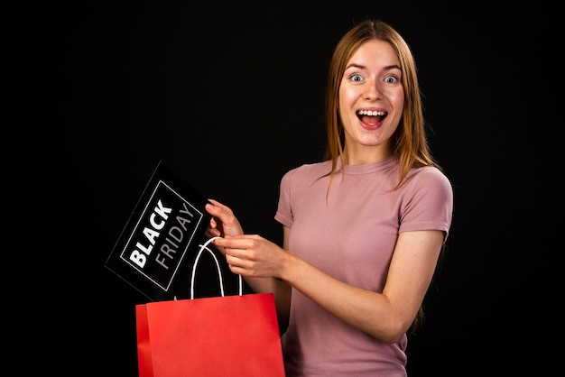 Medium shot of a happy woman holding a black friday card