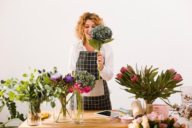 Medium shot happy woman holding a bouquet