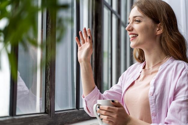 カップを保持しているミディアムショット幸せな女性