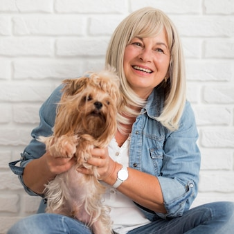 Medium shot happy woman holding dog