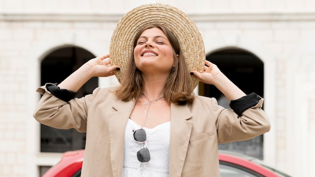 Medium shot happy woman holding hat