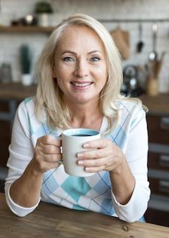 Medium shot happy woman holding a mug