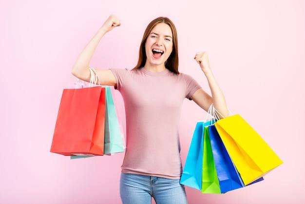Medium shot of happy woman holding shopping bags
