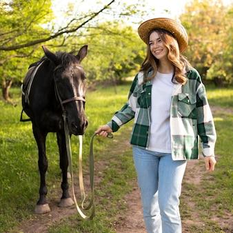 Donna e cavallo felici del tiro medio all'aperto