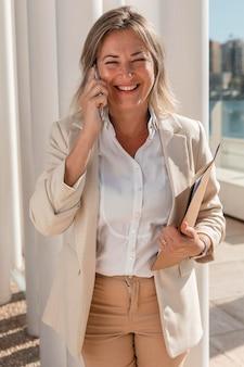 Donna felice del colpo medio sul telefono
