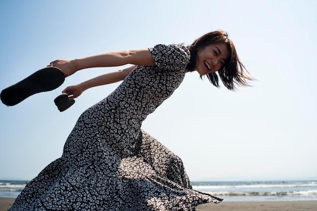 ビーチで走っているミディアムショットの幸せな女性