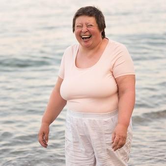 Donna felice del colpo medio in riva al mare