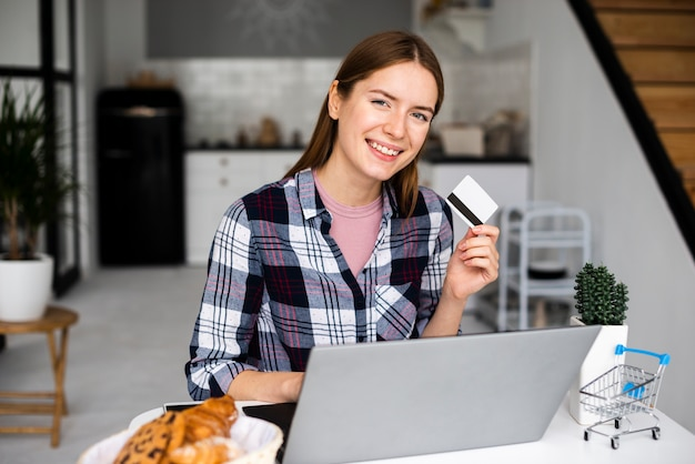 Medium shot happy woman showing credit card