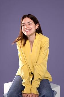 Donna felice del colpo medio che si siede sulla sedia