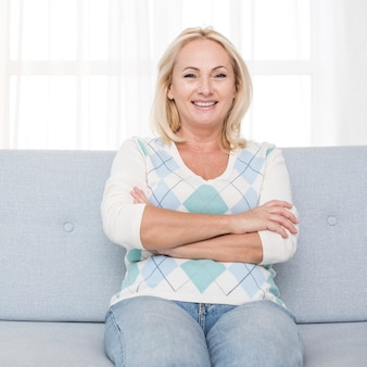 Medium shot happy woman sitting on the couch