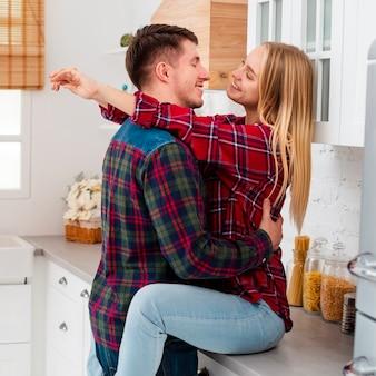 Donna felice del colpo medio che si siede sul controsoffitto della cucina