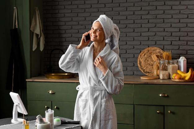 Donna felice del colpo medio che parla sul telefono