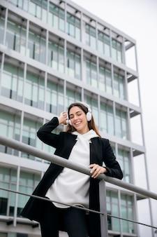 헤드폰을 착용하는 중간 샷 행복 한 여자