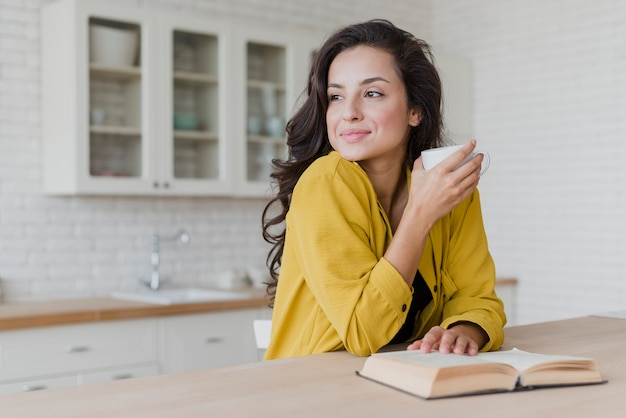 Medium shot happy woman with book looking away