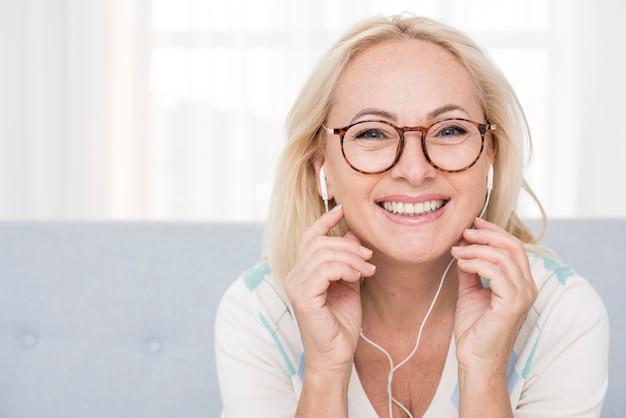 Medium shot happy woman with glasses and headphones