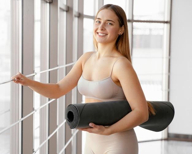 Средний снимок счастливая женщина с циновкой