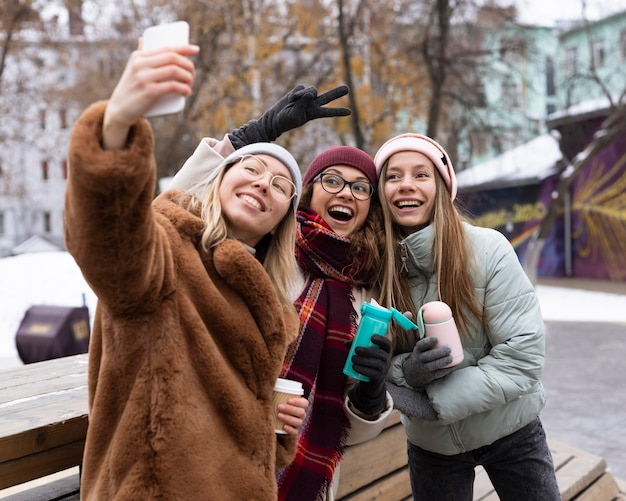 Medium shot happy women taking selfies