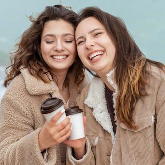 コーヒーカップとミディアムショットの幸せな女性