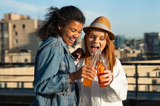 Medium shot happy women with drinks