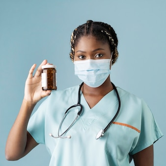 Медицинский работник среднего выстрела, держащий контейнер для таблеток