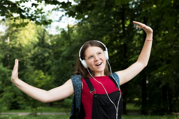 Medium shot of highschool girl dancing while listening to music