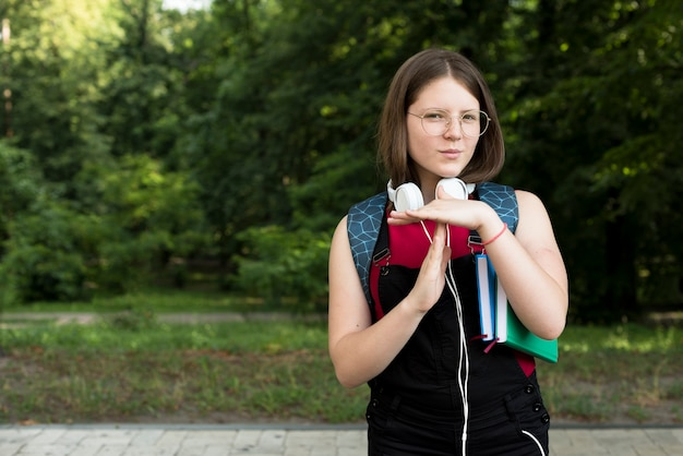 Medium shot of highschool girl holding timeout sign