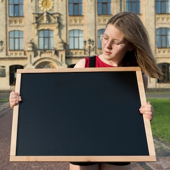 Medium shot highschool girl looking blackboard