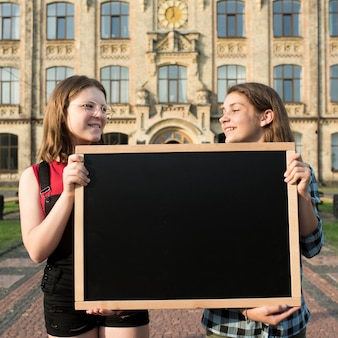 Medium shot highschool girls holding blackboard