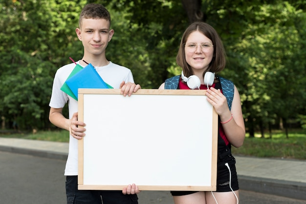 Medium shot highschool students holding whiteboard