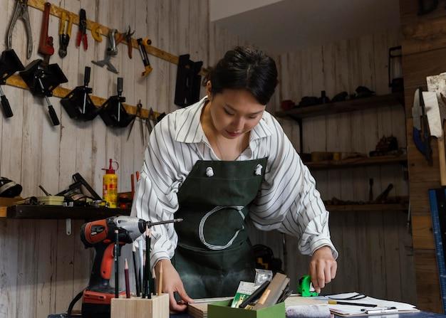 Donna giapponese del colpo medio che misura il legno